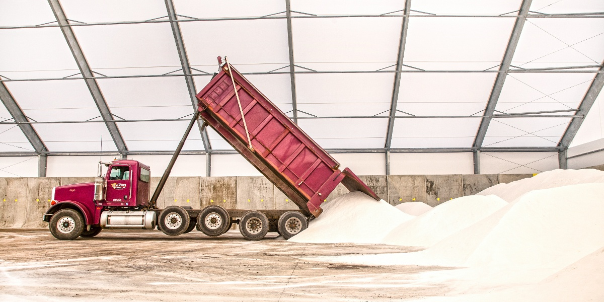 Photo of a truck dumping salt in a fabric storage building